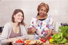 Szczęśliwi przyjaciele gotuje w kuchni Obrazy Stock