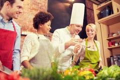 Szczęśliwi przyjaciele i szefa kuchni kucbarski kucharstwo w kuchni Obraz Stock
