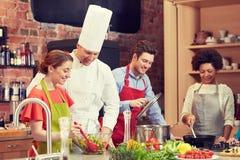 Szczęśliwi przyjaciele i szefa kuchni kucbarski kucharstwo w kuchni Fotografia Royalty Free