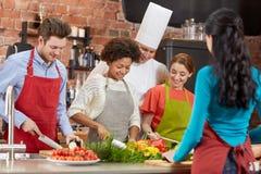Szczęśliwi przyjaciele i szefa kuchni kucbarski kucharstwo w kuchni Zdjęcie Royalty Free