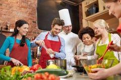 Szczęśliwi przyjaciele i szefa kuchni kucbarski kucharstwo w kuchni Zdjęcia Royalty Free
