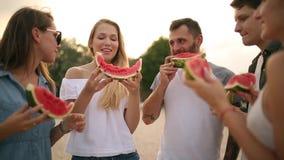 Szczęśliwi przyjaciele Je arbuz pozycję na Piaskowatej plaży i gawędzeniu Młodzi Człowiecy i kobiety Jest ubranym niebieskich dżi zbiory wideo