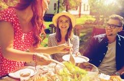 Szczęśliwi przyjaciele ma gościa restauracji przy lata ogrodowym przyjęciem zdjęcia royalty free