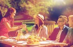 Szczęśliwi przyjaciele ma gościa restauracji przy lata ogrodowym przyjęciem obraz stock