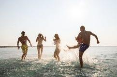 Szczęśliwi przyjaciele ma zabawę na lato plaży Obraz Stock