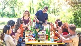 Szczęśliwi przyjaciele ma zabawę przy grilla pinkinu przyjęciem wpólnie - młodzi ludzie millenials przy pic nic na na wolnym powi obrazy royalty free