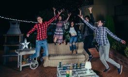 Szczęśliwi przyjaciele ma zabawę wśród partyjnych confetti obraz royalty free