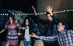 Szczęśliwi przyjaciele ma zabawę wśród partyjnych confetti fotografia stock
