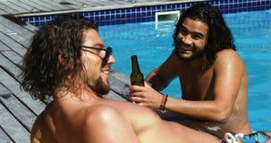 Szczęśliwi przyjaciele oddziała wzajemnie z each inny podczas gdy cieszący się pije poolside zdjęcie wideo