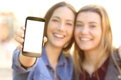Szczęśliwi przyjaciele pokazuje pustego telefonu ekran obraz stock