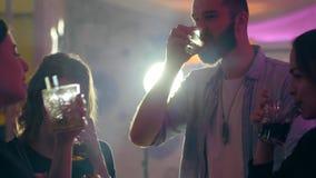 Szczęśliwi przyjaciele robią grzance z napojem w szkłach przy klubem nocnym na tle światła reflektorów zdjęcie wideo