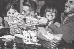Szczęśliwi przyjaciele rozwesela z cockatil w rocznika barze - młodzi ludzie ma zabawę wznosi toast szkła koktajle w pubu klubie obrazy royalty free