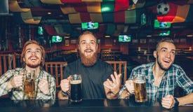 Szczęśliwi przyjaciele siedzi wpólnie przy barem odpierającym w pubie Oglądają w górę przedniego i rozochoconego Faceci kubki piw zdjęcia royalty free
