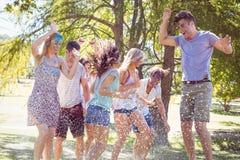 Szczęśliwi przyjaciele skacze w wodnym krótkopędzie Zdjęcia Stock