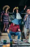 Szczęśliwi przyjaciele tanczy zabawę z kostiumami i ma w przyjęciu zdjęcia stock