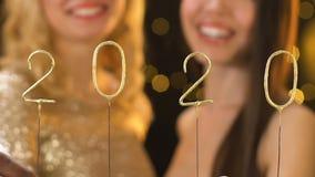Szczęśliwi przyjaciele trzyma 2020 liczb, koledzy świętuje nowego roku, przyjęcie zdjęcie wideo