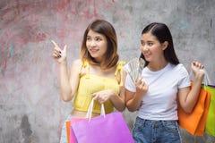 Szczęśliwi przyjaciele trzyma pieniądze z torbami na zakupy Dwa z podnieceniem sklep zdjęcia stock