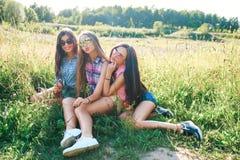 Szczęśliwi przyjaciele w parku na słonecznym dniu Lato stylu życia portret trzy modniś kobiety cieszy się ładnego dzień, jest ubr Obraz Stock