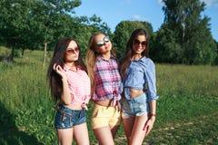Szczęśliwi przyjaciele w parku na słonecznym dniu Lato stylu życia portret trzy modniś kobiety cieszy się ładnego dzień, jest ubr Obraz Royalty Free