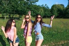 Szczęśliwi przyjaciele w parku na słonecznym dniu Lato stylu życia portret trzy modniś kobiety cieszy się ładnego dzień, jest ubr Obrazy Stock