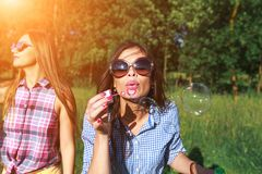 Szczęśliwi przyjaciele w parku na słonecznym dniu Lato stylu życia portret trzy modniś kobiety cieszy się ładnego dzień, jest ubr Zdjęcie Royalty Free