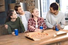 Szczęśliwi przyjaciele wydaje czas wraz z pizzy i sody napojami obraz royalty free