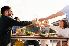 Szczęśliwi przyjaciele wznosi toast napoje przy dachu przyjęciem zdjęcia stock