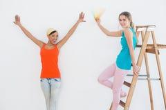 Szczęśliwi przyjaciele z drabinowym wybiera kolorem dla malować pokój Zdjęcie Royalty Free