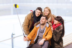 Szczęśliwi przyjaciele z smartphone na łyżwiarskim lodowisku Zdjęcia Stock