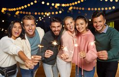 Szczęśliwi przyjaciele z sparklers przy dachu przyjęciem obraz stock