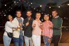 Szczęśliwi przyjaciele z sparklers przy dachu przyjęciem zdjęcie royalty free