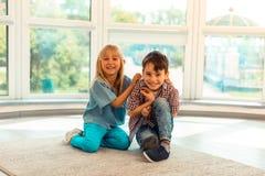 Szczęśliwi radośni dzieciaki siedzi wpólnie na podłodze zdjęcia stock