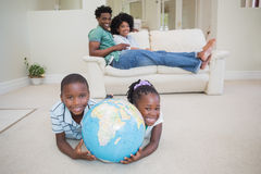 Szczęśliwi rodzeństwa kłama na podłogowej mienie kuli ziemskiej Fotografia Stock