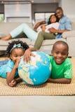 Szczęśliwi rodzeństwa kłama na podłogowej mienie kuli ziemskiej Obraz Royalty Free