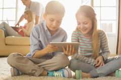 Szczęśliwi rodzeństwa używa cyfrową pastylkę na podłoga z rodzicami w tle Obraz Royalty Free