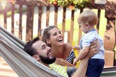 Szczęśliwi rodzice bawić się z ich chłopiec w hamaku zdjęcia stock