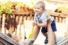 Szczęśliwi rodzice bawić się z ich chłopiec w hamaku zdjęcia royalty free