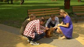 Szczęśliwi rodzice i ich dzieci muska pięknego psa w parku, zwierzę domowe adopcja zdjęcie wideo