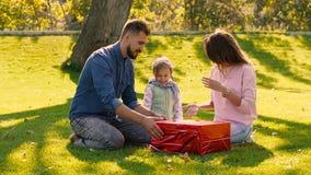 Szczęśliwi rodzice pomaga ich małej dziewczynki otwartej teraźniejszości zbiory wideo