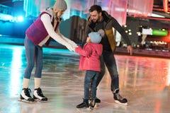 szczęśliwi rodzice uczy uroczego małego córki łyżwiarstwo obrazy stock