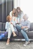 Szczęśliwi rodzice z córkami wydaje ilość czas w żywym pokoju Zdjęcia Royalty Free