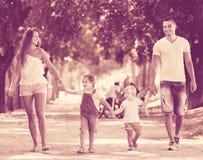 Szczęśliwi rodzice z małymi dziećmi chodzi w parku Zdjęcia Royalty Free