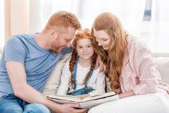 Szczęśliwi rodzice z uroczą małą córką siedzi wpólnie i czytelniczą książką zdjęcie royalty free