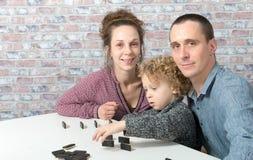 Szczęśliwi rodzinni bawić się domina zdjęcia royalty free
