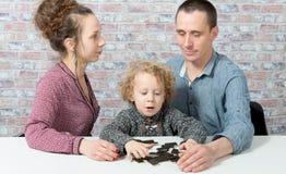 Szczęśliwi rodzinni bawić się domina zdjęcia stock