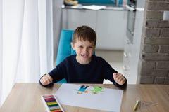 Szczęśliwi 8 rok chłopiec dziecka rysuje kartka z pozdrowieniami dla jego babci Zdjęcia Stock