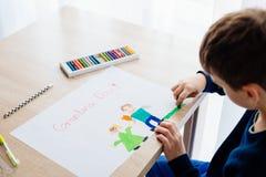Szczęśliwi 8 rok chłopiec dziecka rysuje kartka z pozdrowieniami dla jego babci Zdjęcie Stock