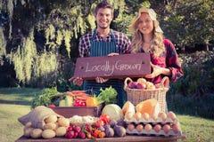 Szczęśliwi rolnicy stoi przy ich kramem obraz royalty free