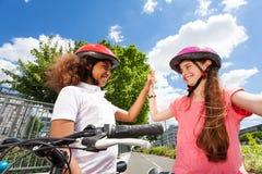Szczęśliwi rowerów jeźdzowie daje wysokości pięć po ścigać się Obraz Stock