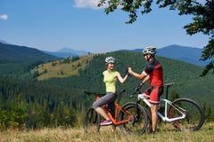 Szczęśliwi rowerzyści dobierają się, mężczyzna i kobiety pod dużą zieloną gałąź pozycja z rowerami na trawiastym wzgórzu, obrazy royalty free